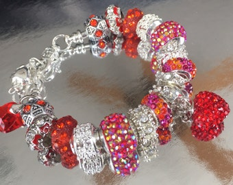 Reddish/orange crystal charm bracelet with dangling heart charm.