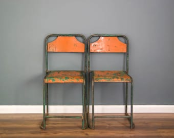 A pair of metal stacking chairs