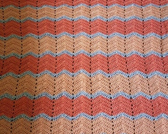 Hand crocheted coral and grey baby blanket.