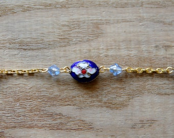 Bracelet. A textured gold plated cable bracelet set with an oval shaped flower designed blue Cloisonne bead, and acrylic bicones. NHC013