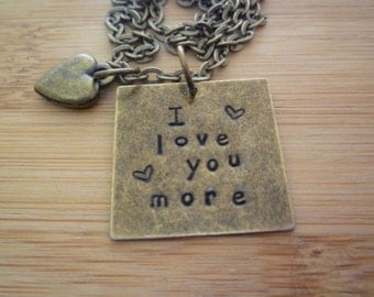 """I LOVE YOU MORE necklace hand stamped on a 1"""" square with a puff heart"""