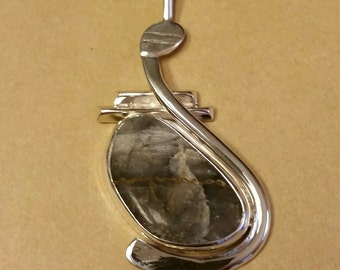 Natural River Rock set in a modern abstract Sterling Silver Pendant with chain.