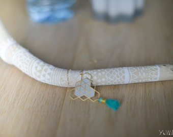 gold plated geometric necklace adorned with iridescent blue leather and petrol blue pompon