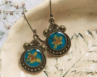 Handwork earrings with fresh flowers on a turquoise background.