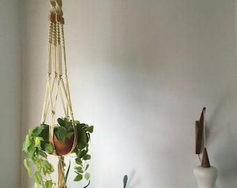 braided macrame planter. mid century boho hanging planter. wood bead braided hanging planter. boho beaded planter plant hanger.