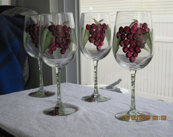 Wine glasses with stems set of four hand painted with purple grapes and green leaves. Grapes are also painted on the bottom of the glass