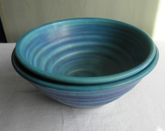 Two modern pottery nesting bowls, bright turquoise blue, one signed