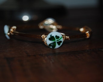 Wire wrapped beaded bracelet, gold with white & green glass beads featuring a shamrock design
