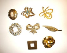 Vintage costume jewelry lot of 8 classic brooches. A carved cameo, a real pearl. The wreath is marked Lisner and the bow-tie marked Gerrys.