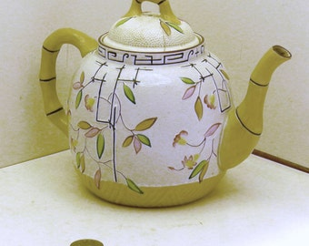 Oriental style majolica, white with colorful flowers and leaves teapot and beautiful.