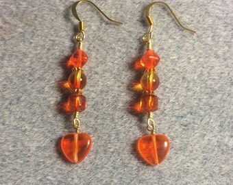 Bright orange Czech glass heart bead dangle earrings adorned with bright orange Czech glass beads.