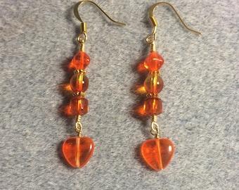 Bright orange Czech glass heart bead dangle earrings adorned with bright orange Czech glass beads.