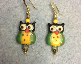 Green and yellow lampwork owl bead earrings adorned with green and yellow Czech glass beads.