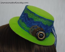 lime green mini top hat with blue lace, gears, and vintage button