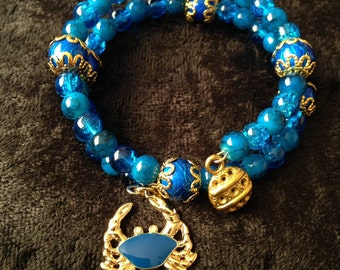 Blue wrap bracelet with blue and gold crab charm