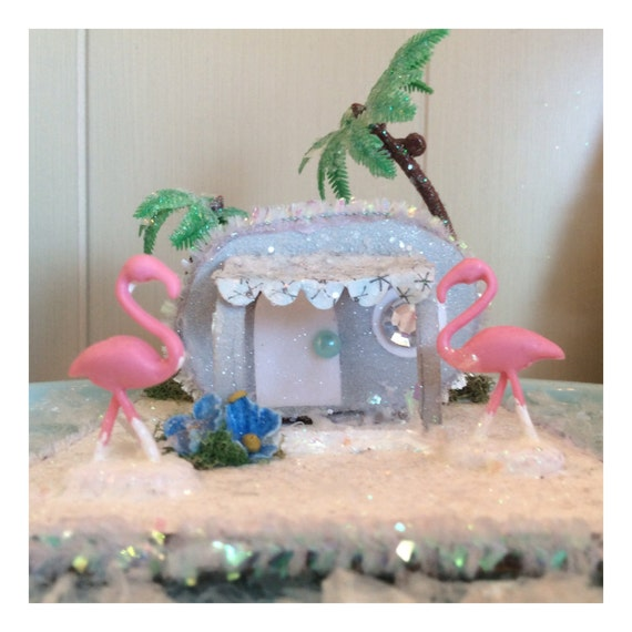 Miniature kitsch glitter house trailer with palm trees and yard flamingos