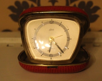 A Lovely 1950's travelling alarm clock, full working order.Red and gold.