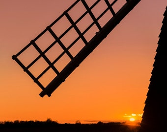 Fine Art Print of the silhouette of a windpump sail at sunset