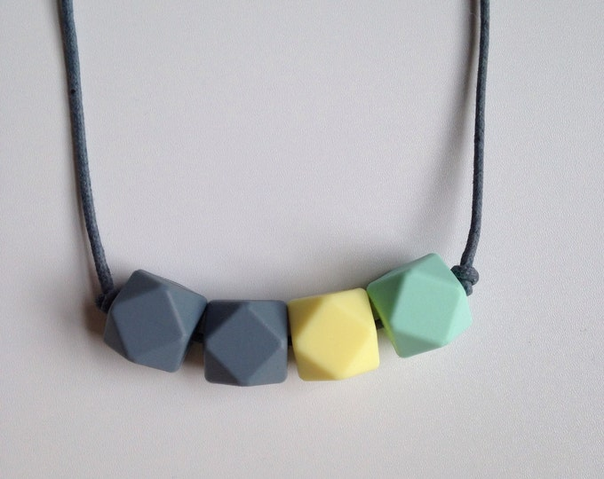 Teething necklace in grey, pale yellow and mint green, made from BPA free chewable silicone hexagon beads by Little Gnashers