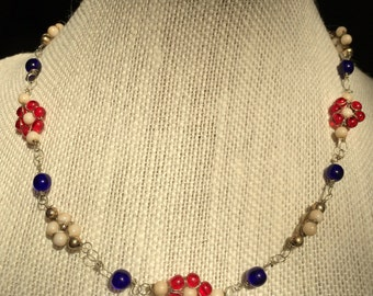 Little flower necklace with red, white, and blue beads with silver colored wire and beads.