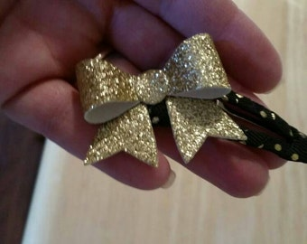 Gold glitter bow on a hair clip wrapped in black ribbon.