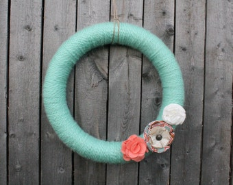 Teal yarn wreath with fabric flowers