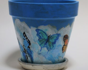 Butterflies in the breeze! Hand painted flower pot - bright pops of color against a cotton ball sky