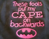 These Fools Put My Cape On  Backwards Batman Bib With Hot Pink Lettering