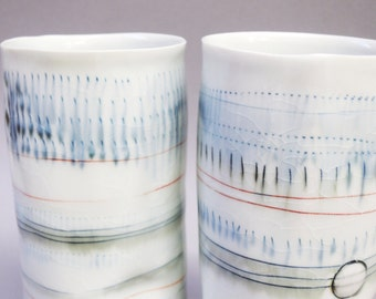 Two Tall porcelain tumblers with translucent bottom