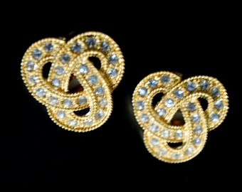 Luxurious vintage 80s gold tone textured metal celtic knot , large clip on earrings with a clear rhinestones. Made by Avon.Mint condition.