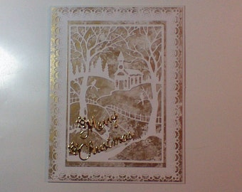 Christmas card with church,trees, birds and fence in gold and white.