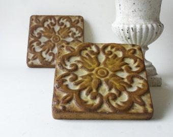 two cement fleur de lis pattern tile