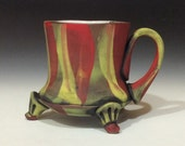 Dry exterior flaming red and yellow mug with black accents and feet