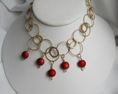 Eye-catching gold hoops with deep red dangles statement necklace