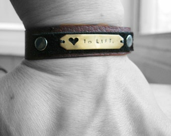 Lift - unisex, black, brown layered leather cuff, stamped metalwork tag, snap or studded closure, custom fit