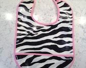 Zebra-print bib with pink trim and pocket