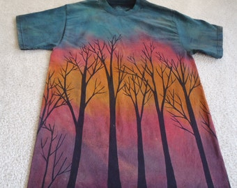Sunset through the trees on a winter's night, tree silhouettes against orange, fuchsia, raspberry and blues, man's medium discharged t-shirt