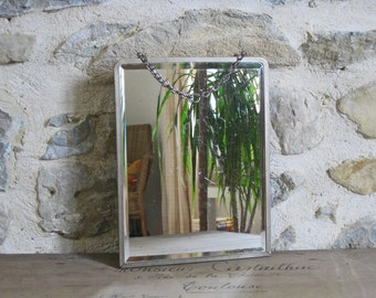 French vintage mirror with delicate engraved silver metal frame and patterned back