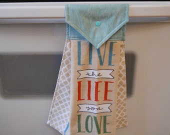 """Hanging lovely kitchen towel with """"live the life you love"""" on the front."""