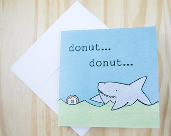 "CARD: ""Donut Shark 1, Shark Chasing Donut"" featuring a happy shark chasing after a frosted, sprinkled donut in the sea"
