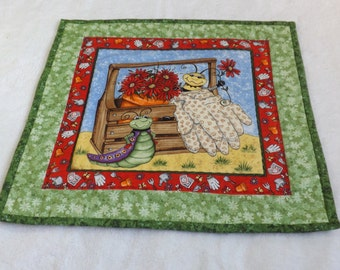 Quilted gardener's wall hanging with bee,  caterpillar, flowers, gardening gloves, and tools