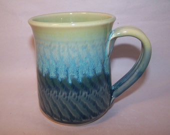 Wheel thrown stoneware mug. Glaze Green Chattering.  Approx.10m height.  Capacity 300ml.