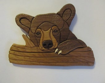 Intarsia bear cub on log
