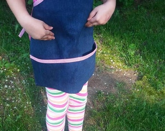 Navy blue denim childrens apron trimmed red checked bias binding. Large pockets. Fits 5 to 10 year old boys or girls.