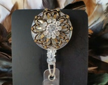 Fanciful.  Fun Bronze and Rhinestone Retractable Reel Badge and ID Holder.