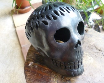 Small black clay skull made in Mexico.  Carved out design.