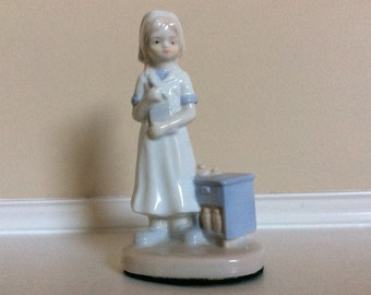 A Glossy Porcelain Nurse Figurine with a Pen and Chart in her hands.