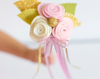 Flower girl wand in pastel pink, cream and gold featuring a trio of felt roses, gold leaves and ribbon.