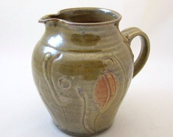Stoneware pitcher, thrown on the wheel and hand-carved, with slip trail decoration, shino glaze.