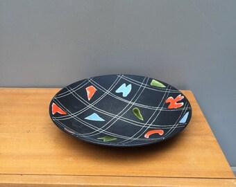 Black ceramic plate. 50s. Ceramic dish. Retro. Vintage.